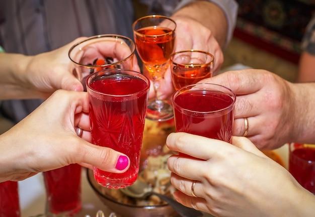 사람들은 테이블에서 술을 마시고 잔을 땡땡이칩니다. 건배