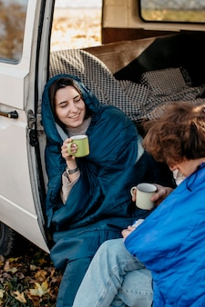 People drinking coffee inside their van