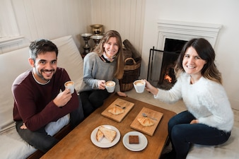People drinking coffee near fireplace