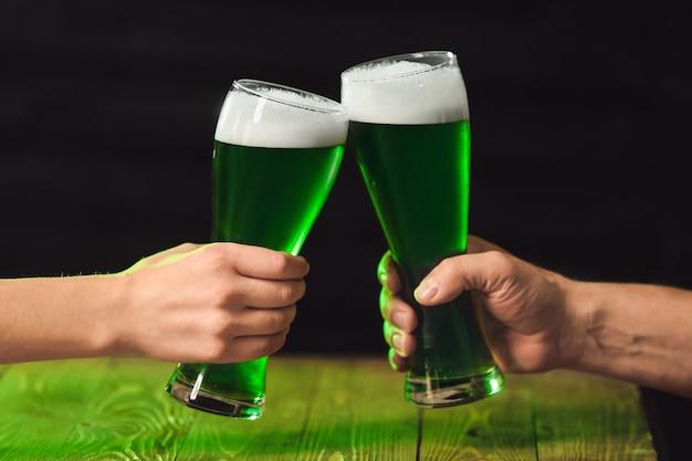 Люди пьют зеленое пиво в пабе в день святого патрика