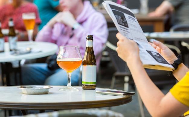 人々は古いヨーロッパの観光の町のストリートカフェでビールを飲みます。