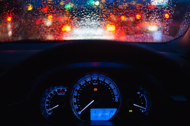 People driving modern car in night time with light and drop of water bokeh at raining day