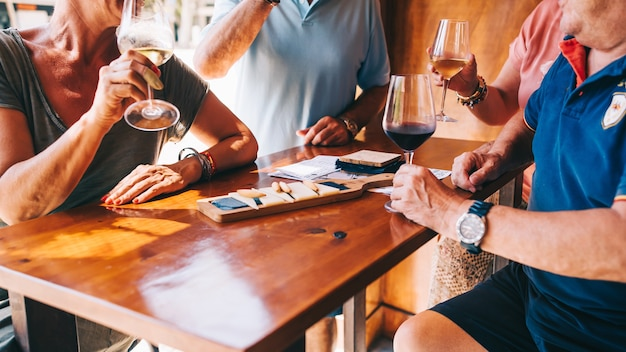 Люди едят сыр и пьют вино в ресторане на террасе в солнечный день.