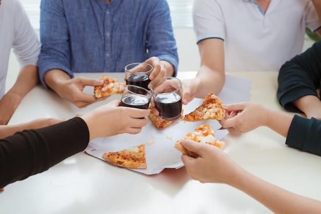 人々はファーストフードを食べます。ピザのスライスを取る友人の手