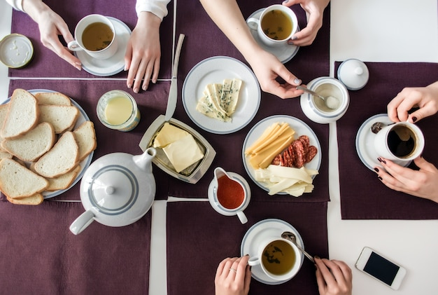 People eat healthy meals with tea and coffee at white served table.
