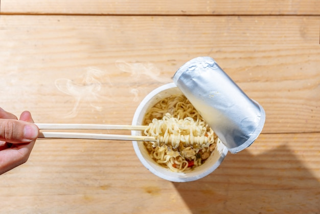 People eat the instant cup noodles with chopstick