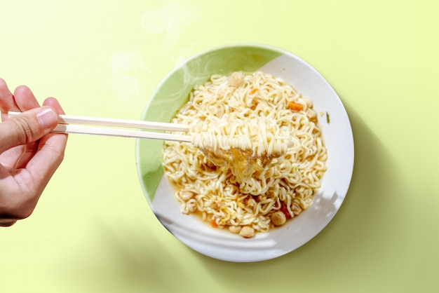 People eat the noodles with chopsticks