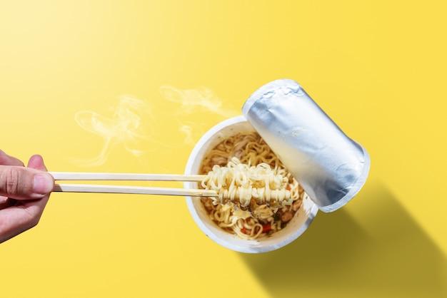 Люди едят лапшу быстрого приготовления с палочками