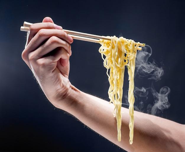 Люди едят лапшу с палочками для еды