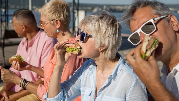 屋外でハンバーガーを一緒に食べる人