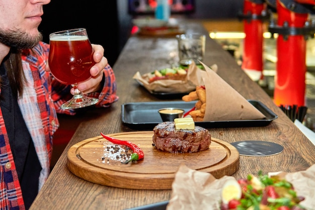 People eating at fast food spending time together in cafe, beer pub. entrecote beef grilled steak meat on wooden cutting boardon with  pepper and salt with bear at the bar counter.