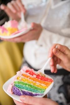 Люди едят домашний красочный вкусный радужный торт