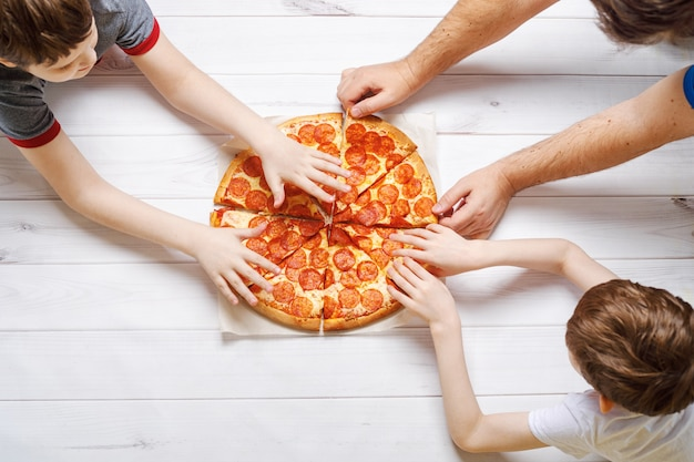 People eating pepperoni pizza.