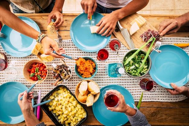 縦から見た食べ物でいっぱいのテーブルで友情や家族のお祝いで一緒に食べる人々