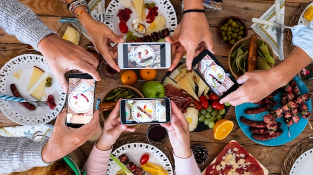 People eating together taking food picture with smartphone to share on social media