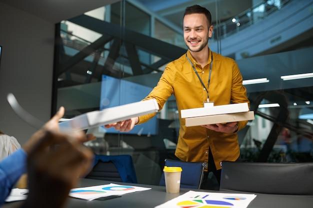 사람들은 it 사무실에서 피자, 비즈니스 점심을 먹습니다. 전문 팀워크 및 계획, 그룹 브레인스토밍 및 기업 작업, 배경에 현대적인 회사 내부