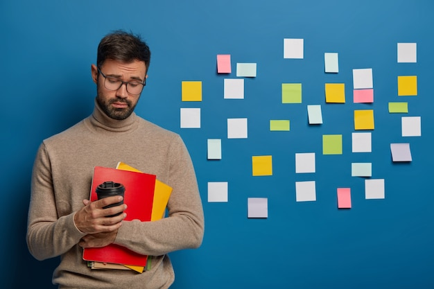 人、教育、知識の概念。無精ひげを持った悲しい不満の男は、試験のために詰め込んだ後、疲れを感じます