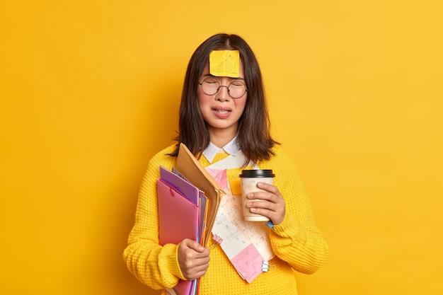 Persone e concetto di educazione. la studentessa asiatica sconvolta si sente stanca della preparazione all'esame beve caffè da asporto fa adesivi memo ha cattivo umore non riesce a ricordare tutto contiene cartelle con documenti