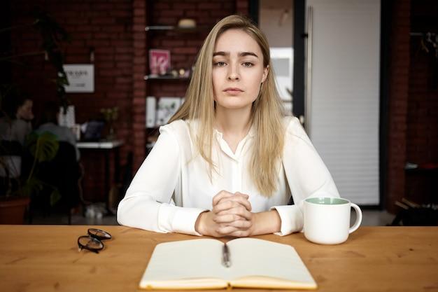 人、教育、仕事、フリーランスのコンセプト。スタイリッシュな若い女性のフリーランサーまたは学生の女の子がカフェのテーブルに座って、コーヒーを飲み、友人やクライアントを待って、彼女の前でコピーブックを開きます
