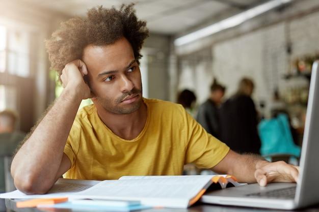 人、教育、現代のテクノロジー、若者のコンセプト。カフェに座っている彼の手に寄りかかって思慮深い顔をしているラップトップの画面に巻き毛が集中している浅黒い肌の混血男性