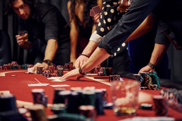 People in elegant clothes standing and playing poker in casino together