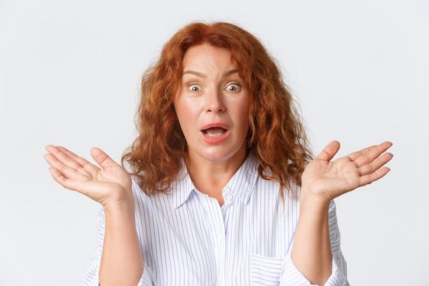 人、感情、ライフスタイルのコンセプト。混乱してショックを受けた赤毛の女性のクローズアップは理解できず、困惑し、手を横に広げて口を開けて心配しているように見えます。