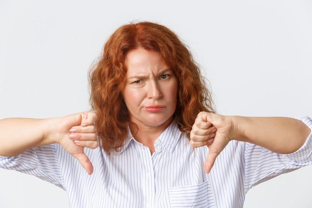 사람, 감정 및 라이프 스타일 개념. 실망하고 화가 났으며 찡그린 중년 빨강 머리 여자가 귀찮고 재미없고 엄지 손가락을 아래로 내리고 싫어하고 반대하는 제스처를 보여주는 확대합니다.