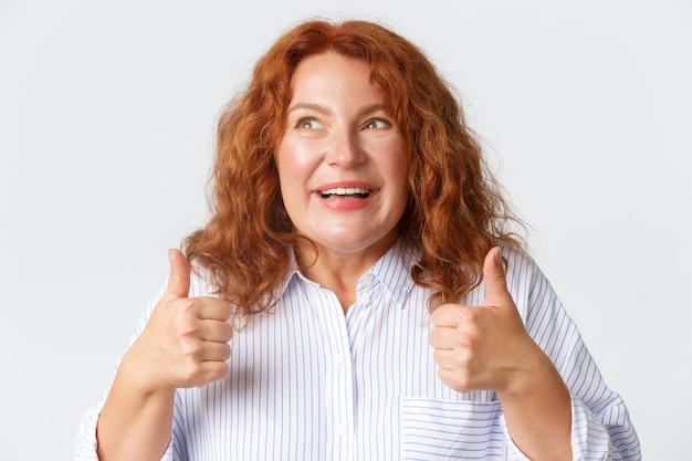 人、感情、ライフスタイルのコンセプト。肯定的な感情でいっぱいの興奮して幸せな赤毛の女性のクローズアップ、親指を立てて喜んでいる様子を見せて、何かをお勧めします。