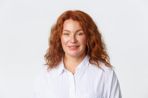 Люди, эмоции и концепция образа жизни. крупный план женщины средних лет с рыжими вьющимися волосами, одетой в повседневную блузку и улыбающейся в камеру, веселая, стоя на белом фоне. копировать пространство