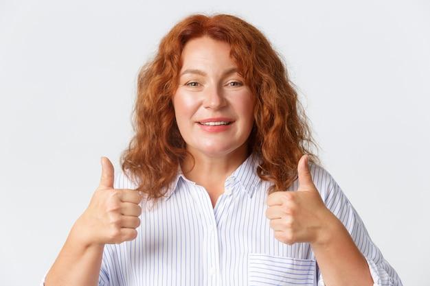 人、感情、ライフスタイルのコンセプト。白い壁に立って、希望に満ちた喜ばしい表情で親指を立てたブラウスを着た、満足のいく笑顔の中年赤毛の女性のクローズアップ。