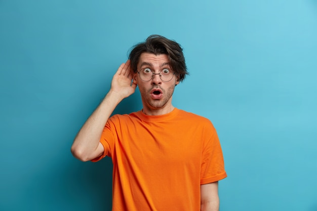 사람, 감정 및 라이프 스타일 개념. 놀란 놀란 남자는 경이로움에서 말을 풀고, 눈을 멍하니 입을 벌리고, 끔찍한 소식을 듣고, 주황색 티셔츠를 입고 투명한 안경을 쓰고 있습니다.