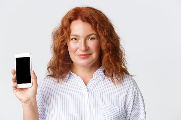 人、感情、テクノロジーのコンセプト。かなり中年の女性、スマートフォンの画面を表示し、笑顔の赤い髪の母親のクローズアップ。女性はチャイルドコントロールアプリケーションをお勧めします。
