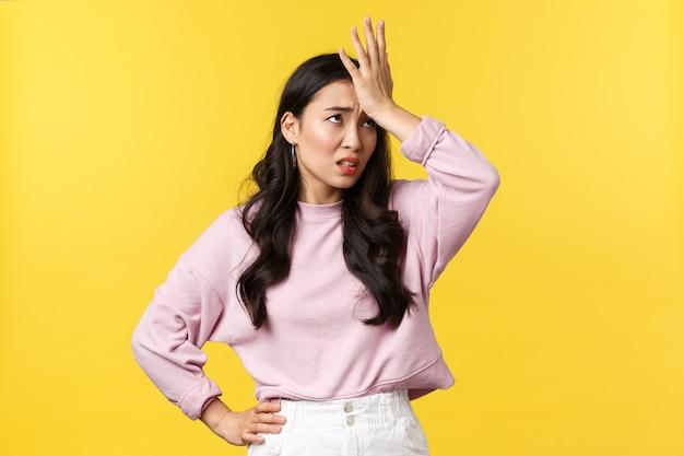 사람들의 감정, 라이프 스타일 및 패션 개념. 짜증나고 성가신 아시아 여성이 이마를 때리고 눈을 굴리고 불쾌한 것을 기억하고 당황한 노란색 배경에 서 있습니다.