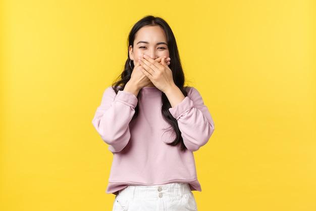 Люди эмоции, образ жизни и концепция моды. веселая смешная корейская женщина смеется, прикрывая рот ладонями, посмеиваясь над забавной шуткой, стоя желтая стена приподнятая