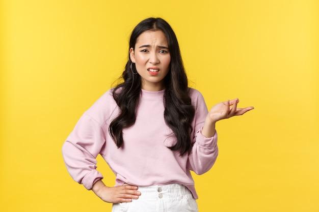 사람들의 감정, 라이프 스타일 및 패션 개념. 세련된 옷을 입은 혼란스럽고 인상 깊지 않은 한국 소녀, 말다툼, 대화, 경악한 표정으로 손을 들고 어깨를 으쓱하고 회의적인 표정