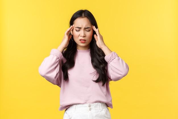 人々の感情、ライフスタイル、ファッションのコンセプト。苦しんで疲れ果てたアジアの女性は目を閉じて寺院に触れ、片頭痛を持って、頭痛やめまい、黄色の背景を感じています。