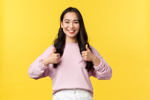 Люди эмоции, образ жизни и концепция моды. взволнованная и довольная жизнерадостная азиатка в стильной одежде, одобрительно показывающая большие пальцы, поддерживает вас, рекомендует промо