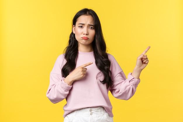 사람들의 감정, 라이프 스타일 및 패션 개념. 우울한 아시아 여성이 손가락을 오른쪽으로 가리키고 후회나 실망으로 몸을 움츠리며 노란색 배경에 슬퍼합니다.