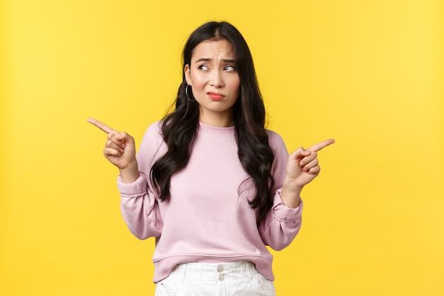 人々の感情、ライフスタイル、ファッションのコンセプト。選択に問題を抱えている優柔不断な問題を抱えたアジアの女性、指を横に向け、笑い声が質問され、左を見て、決定し、黄色の背景。