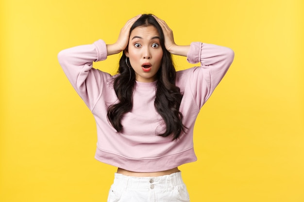 Эмоции людей, образ жизни и концепция моды. ошеломленная и потрясенная азиатская девушка хватается за голову и реагирует на важные новости, говоря «вау», изумленно глядя в камеру, желтый фон.