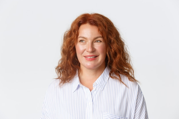 People, emotions and lifestyle concept. dreamy and happy middle-aged redhead woman in blouse smiling pleased, looking left with hopeful gaze, standing white background daydreaming.