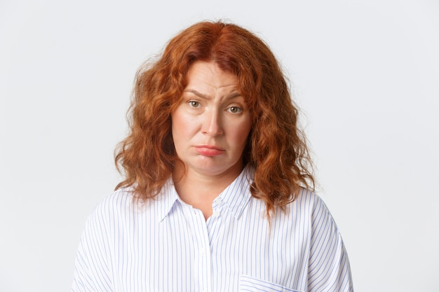 People, emotions and lifestyle concept. unamused tired redhead middle-aged woman making sad face and looking at camera reluctant, standing gloomy over white background. copy space