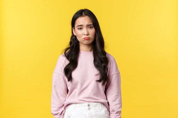 People emotions, lifestyle and fashion concept. depressed and sad, gloomy korean girl pouting, looking down in dumps, feeling upset and displeased, standing yellow background.