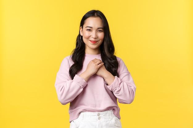 Emozioni della gente, stile di vita e concetto di moda. toccata bella donna coreana che sembra lusingata e felice, tenendosi per mano sul cuore e sorridente, riceve un regalo, in piedi sfondo giallo.