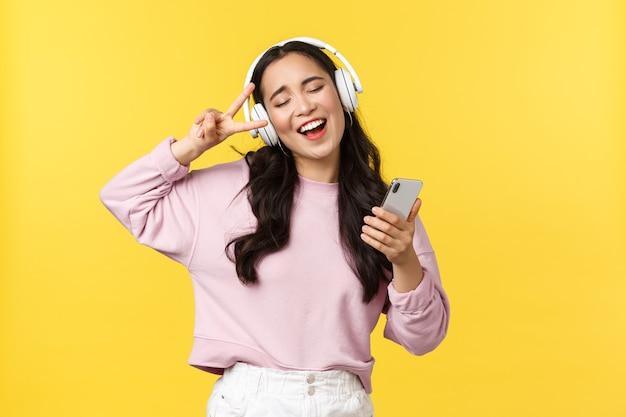 人々の感情、ライフスタイルのレジャーと美しさの概念。のんきな格好良いアジアの女性は目を閉じて、スマートフォンでリラックスして踊り、ヘッドフォンで音楽を聴き、カラオケを歌います。