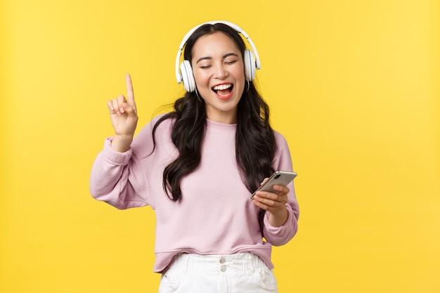 사람들의 감정, 라이프 스타일 여가 및 아름다움 개념. 평온한 행복한 아시아 여성은 무선 헤드폰으로 음악을 듣고, 휴대폰을 들고, 좋아하는 노래를 따라 노래하고, 노란색 배경입니다.