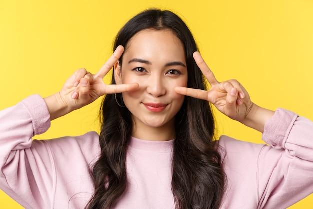 Эмоции людей, досуг образа жизни и концепция красоты. крупный план оптимистичной азиатской девушки каваи делает знаки мира над глазами и улыбается, показывает позитивное счастливое выражение, желтый фон.