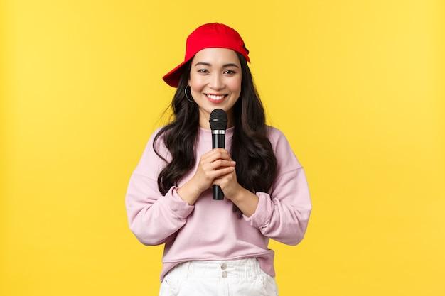 人々の感情、ライフスタイルのレジャーと美しさの概念。赤い帽子で歌を歌う、スピーチをするか、ラップを歌うようにマイクを持って、黄色の背景に立って、かわいい笑顔のアジアの女性パフォーマー