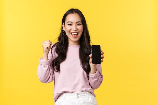 Эмоции людей, досуг образа жизни и концепция красоты. возбужденная и счастливая милая азиатская девушка поет, торжествует кулаком и показывает дисплей мобильного телефона, рекомендует приложение или игру для смартфона.