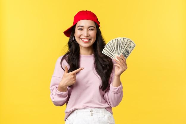 사람들의 감정, 라이프 스타일 레저 및 뷰티 개념. 현금을 자랑스럽게 가리키는 빨간 모자에 행복 매력적인 20 대 여자. 만족 된 아시아 여자 온라인 돈을 버는 방법을 말해